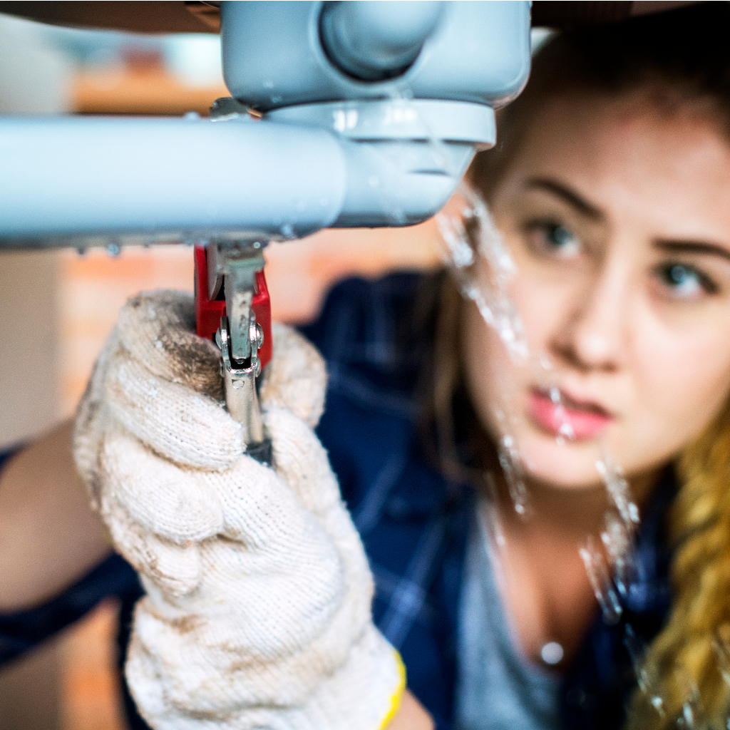 Woman fixing leaking kitchen sink with plumbing tools