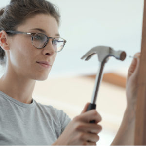 Woman repairing a door at home using a hammer: home renovation and DIY concept