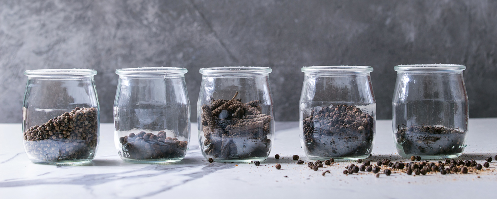 Black pepper in jars on marble countertop