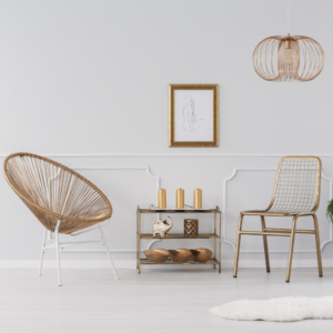 Gold accent chair, coffee table and lighting against white backdrop
