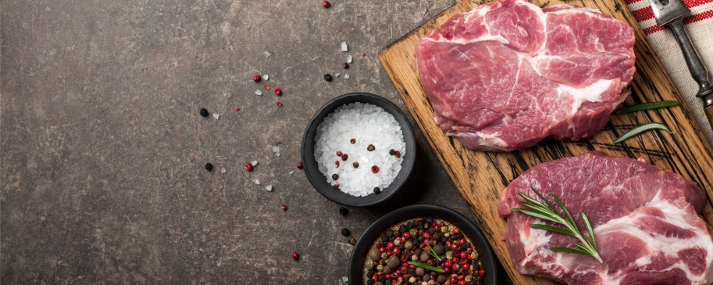 Raw red meat on wooden chopping board with rosemary garnishing, salt, pepper and spices