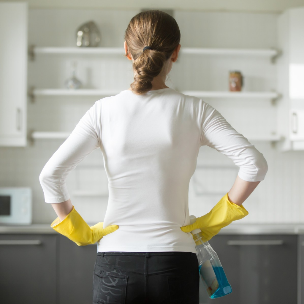 Lady in white with yellow gloves with cleaning detergent