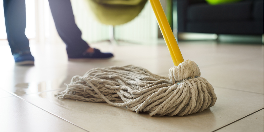 Woman at home, doing chores and housekeeping, wiping floor with water in living room. Focus on floor and mop