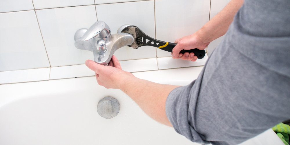 Plumber installing faucet during bathroom renovation