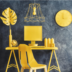 Lamp above chair and desk with camera and computer against concrete wall with clock in modern yellow workspace interior