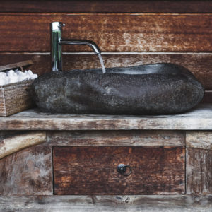 Unique dark natural stone sink with rustic wooden elements for bathroom