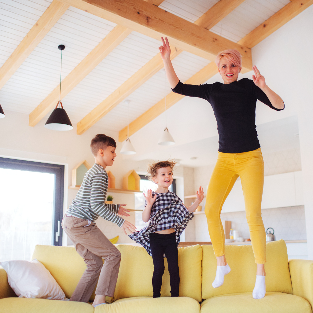 A young mother and two children having fun jumping on yellow sofa