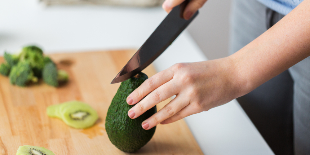 healthy eating, diet and cooking concept - close up of woman hands with knife chopping avocado on cutting board