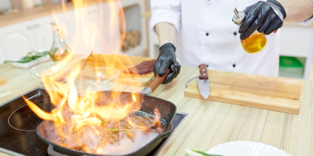 Flaming frying pan in hands of professional chef cooking in modern restaurant kitchen
