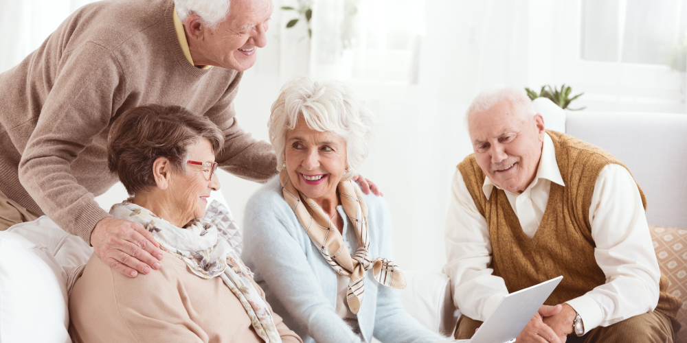 Happy pensioners of senior house using computer