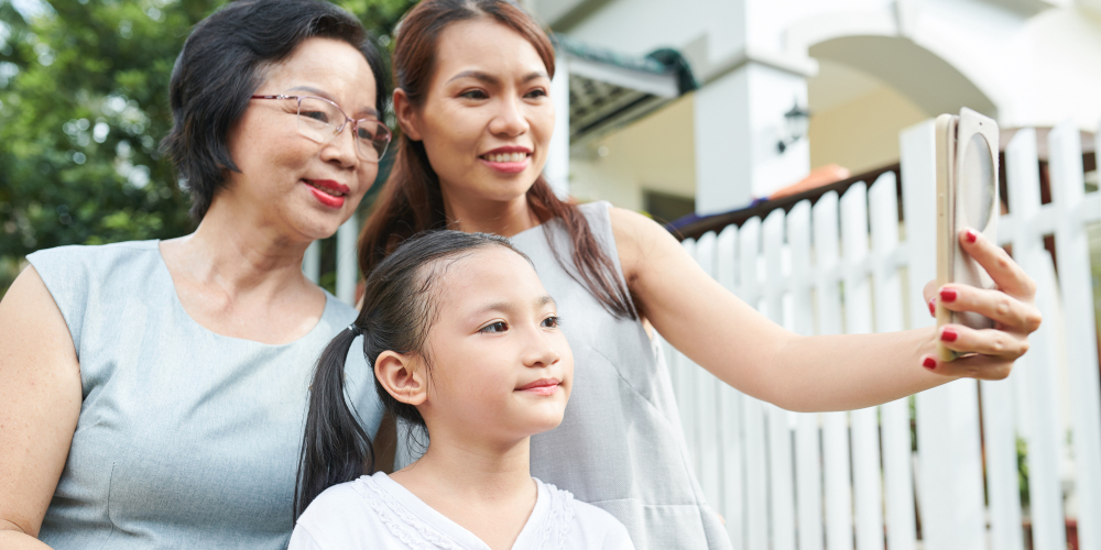 Asian family of three mother daughter and grandmother posing on mobile phone for selfie portrait while spending time outdoors