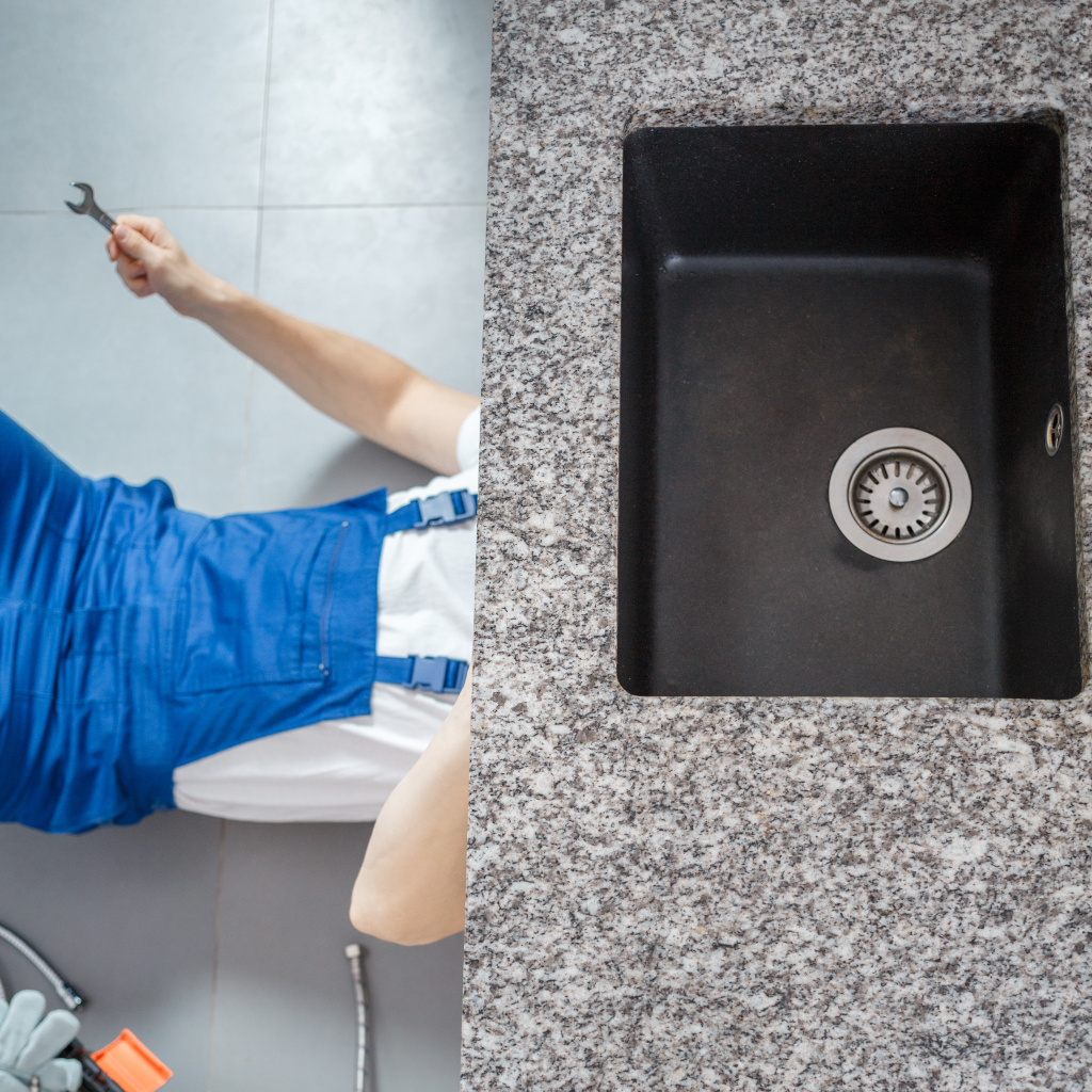 Plumber repairing a leaking kitchen sink