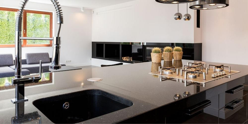 Black quartz countertop with granite composite sink