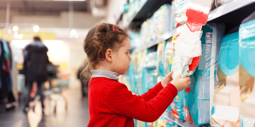Little girl selects diapers in supermarket.