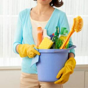 Brushes and bottles with detergents and cleaners in bucket in hands of maid