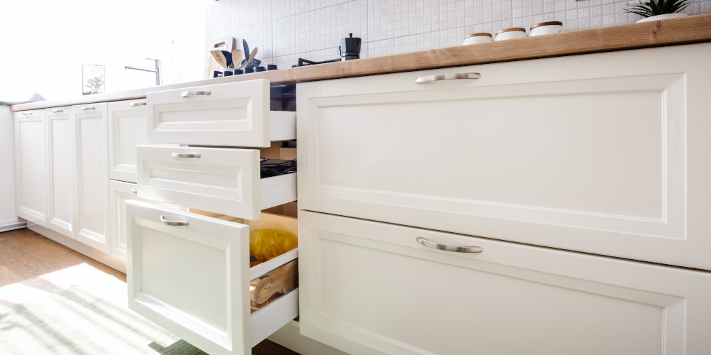 Modern kitchen cabinets and open drawers in white