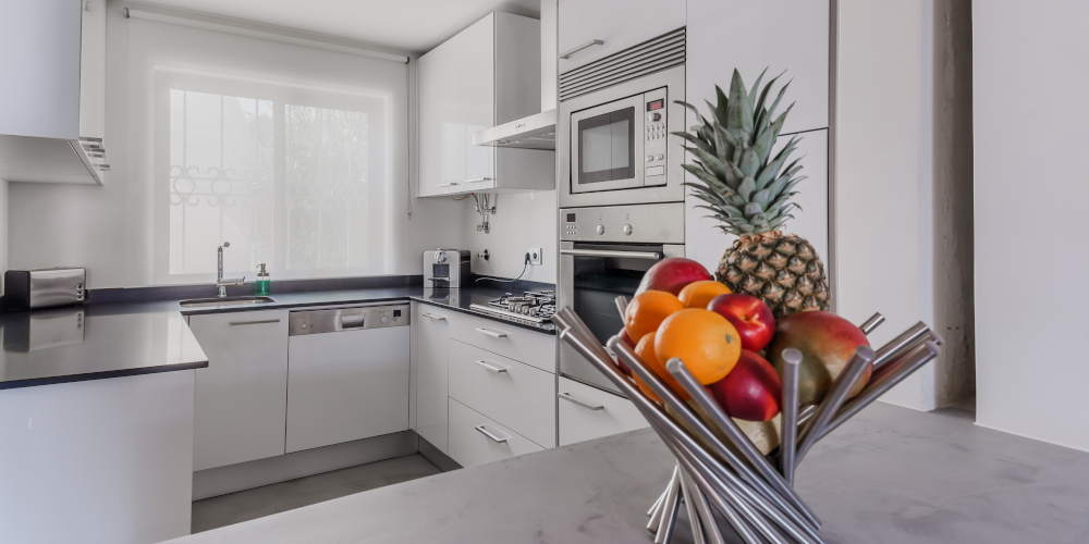 Newly renovated kitchen in a modern apartment with white walls and light grey floor