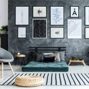 Pouf on striped rug in grey living room interior with gallery of posters and green mattress