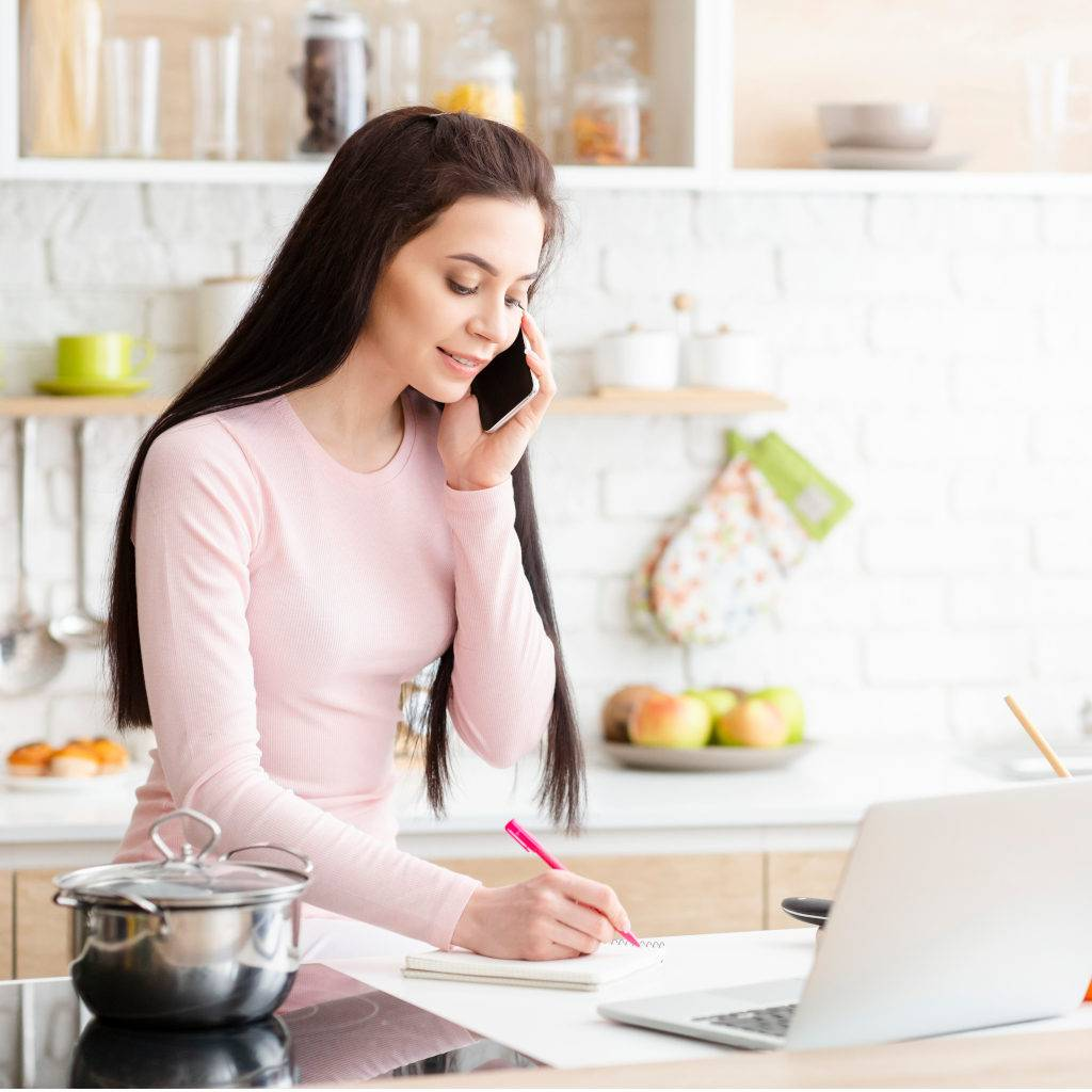 Young lady working from home at her kitchen counter