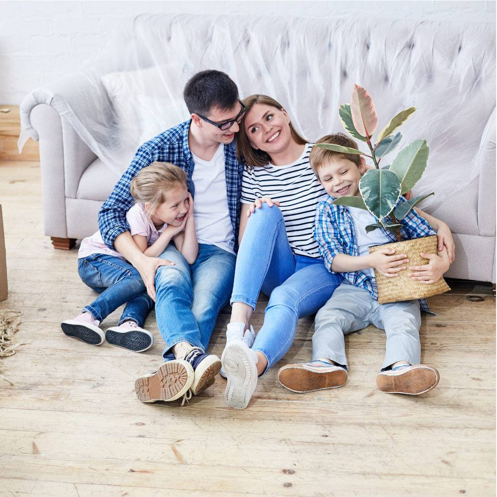 Happy and loving young family gathered together in living room of new apartment and sharing ideas concerning interior design, cute little boy holding houseplant in hands