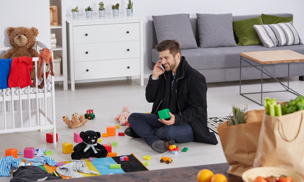 Happy single father sitting on a floor with children toys in the playroom