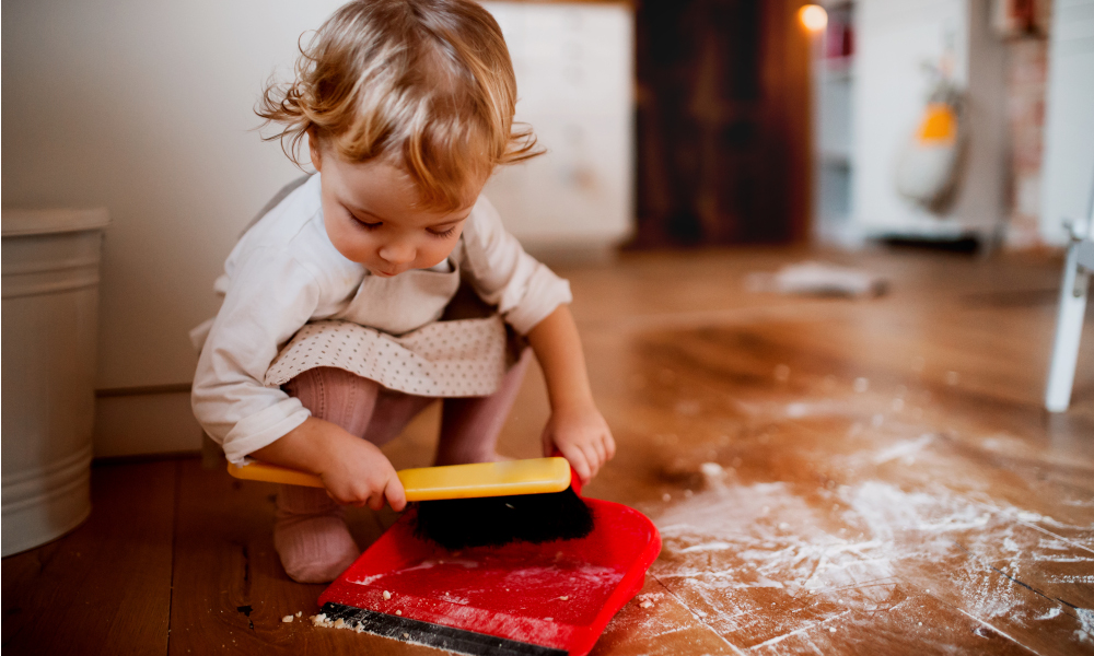 A small toddler girl with brush and dustpan sweeping messy floor in the kitchen at home.