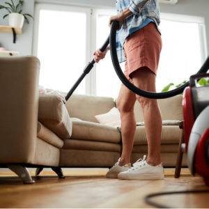 Lady cleaning sofa with vacuum cleaner while removing dust and fur in living room
