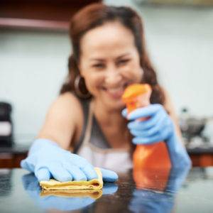Smiling housewife cleaning table surface in kitchen with spray