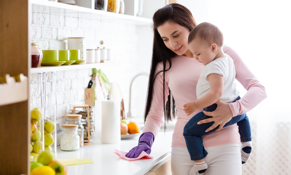 Young mother carrying a baby and cleaning the kitchen countertop