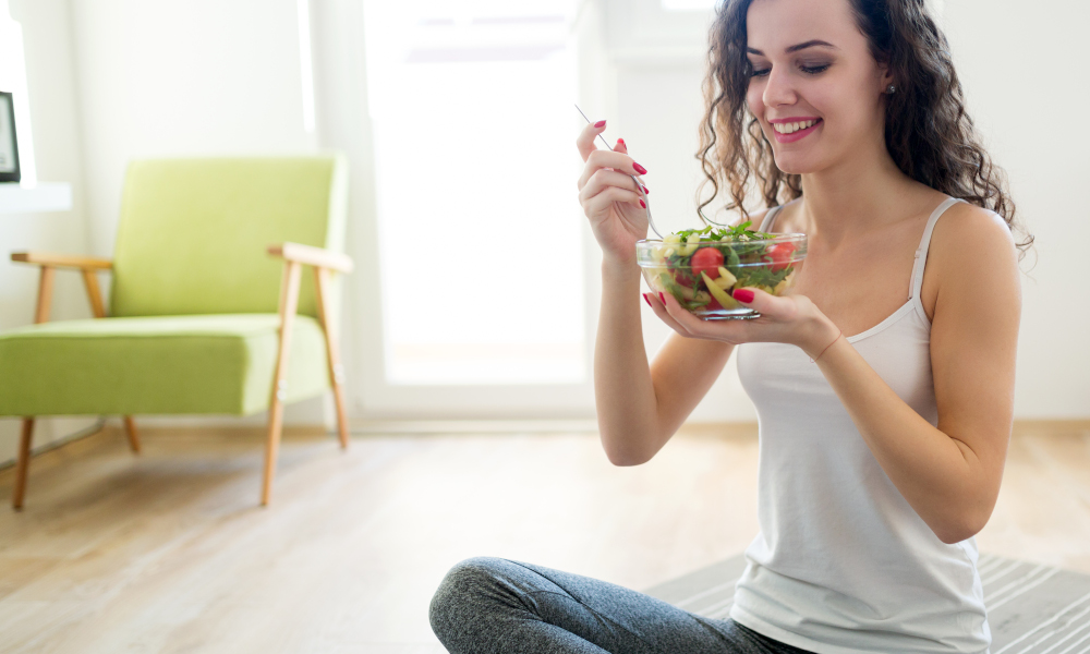 Fitness young woman staying healthy eating a salad after exercise