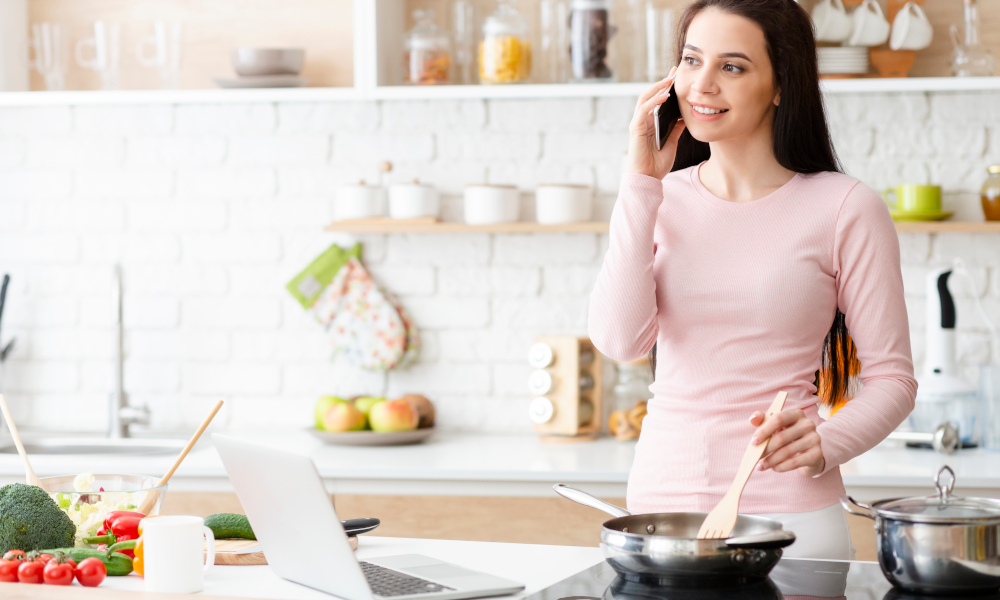 Woman cooking a meal while working from home