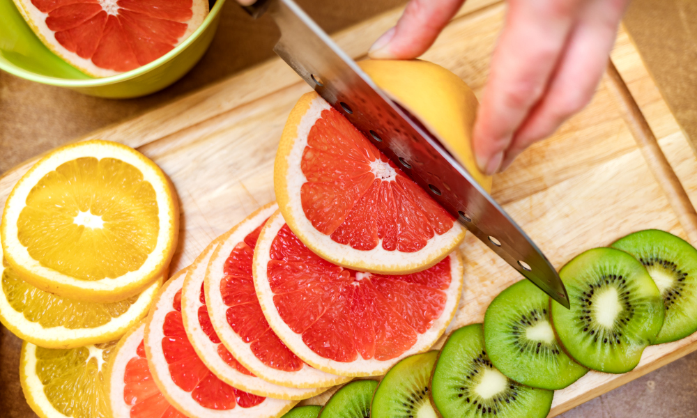 Lady cutting grapefruits with a knife on the cutting board
