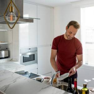 Young beautiful man washing dishes in the sink at home in a modern kitchen