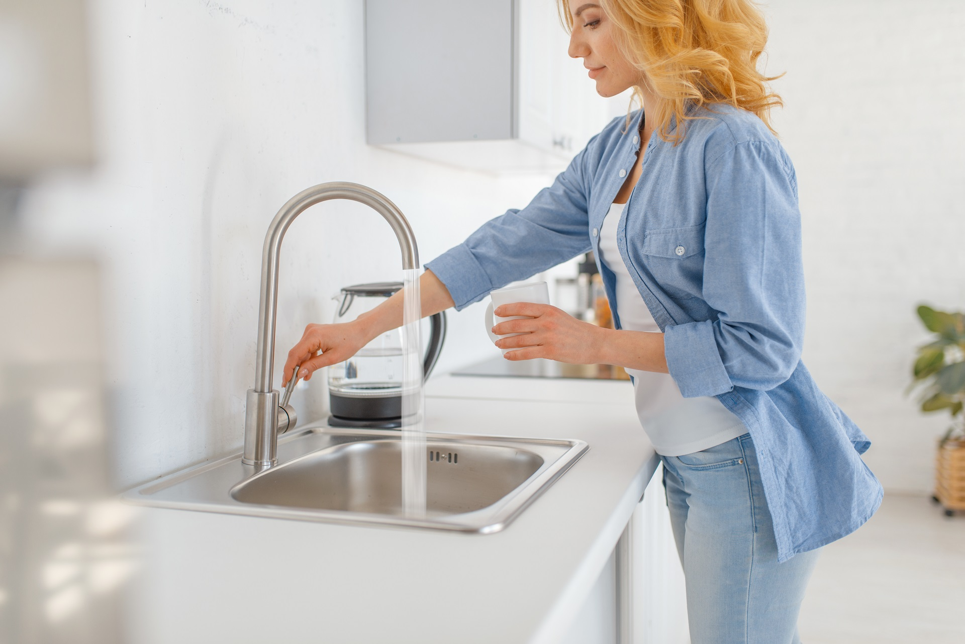 Young woman with glass at the sink on the kitchen. Female person drinks fresh water at home in the morning, healthy nutrition and lifestyle