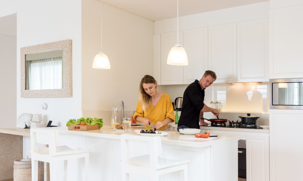 Couple making lunch on a white island kitchen at home