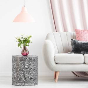 Metal side table with bouquet in a vase next to a white sofa with pastel cushions and empty wall in a living room interior