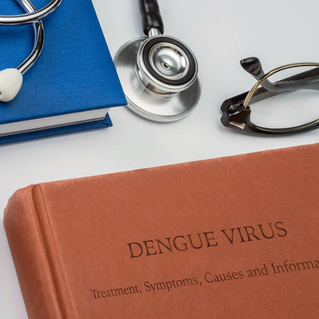 Dengue treatment, symptoms, causes and information written in a medicine book with stethoscope and vintage glasses