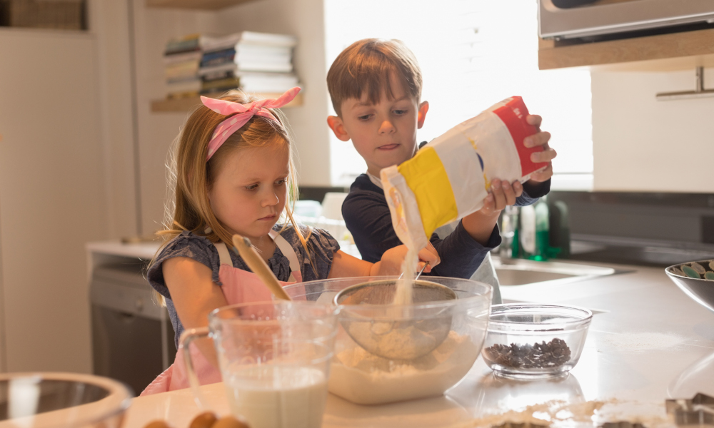 Cute siblings working together to bake cookies in modern kitchen at home