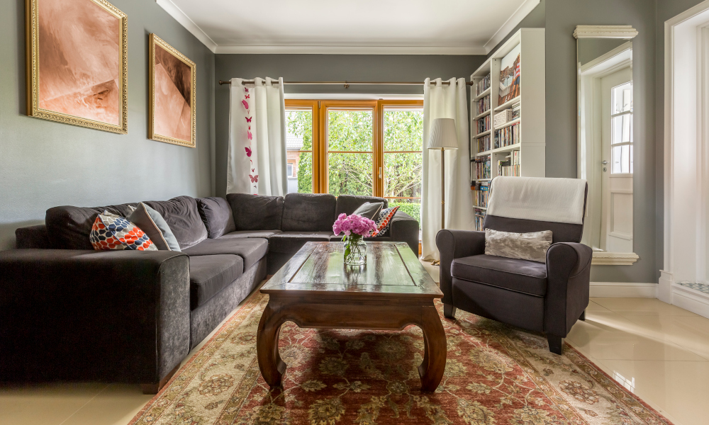 Comfortable living room interior with gray corner sofa and classic coffee table