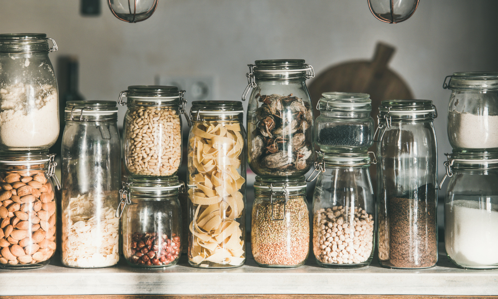 Dried food in glass jars on kitchen countertop