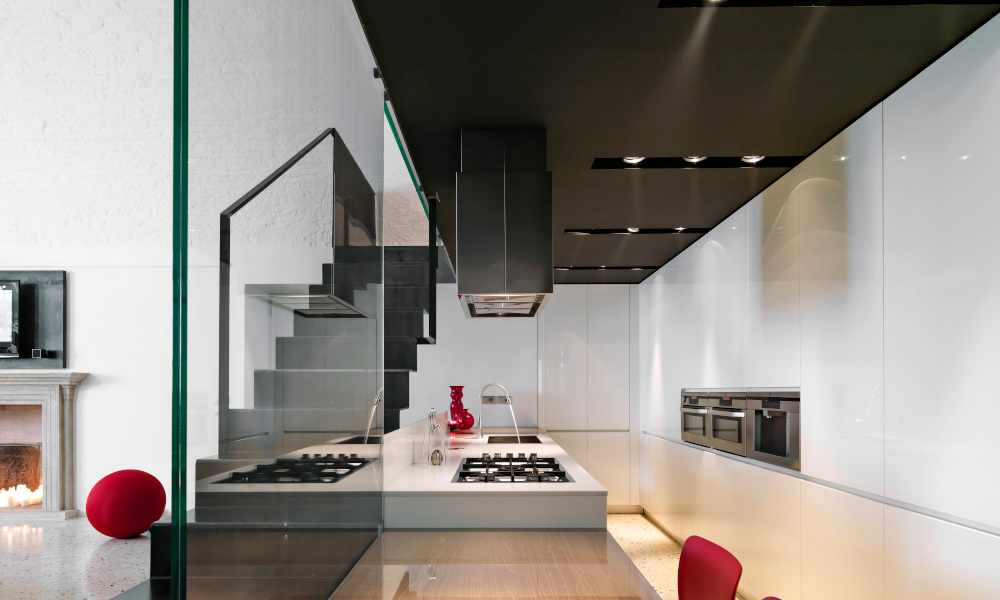 Interior view of a galley style modern kitchen with kitchen island and iron staircase