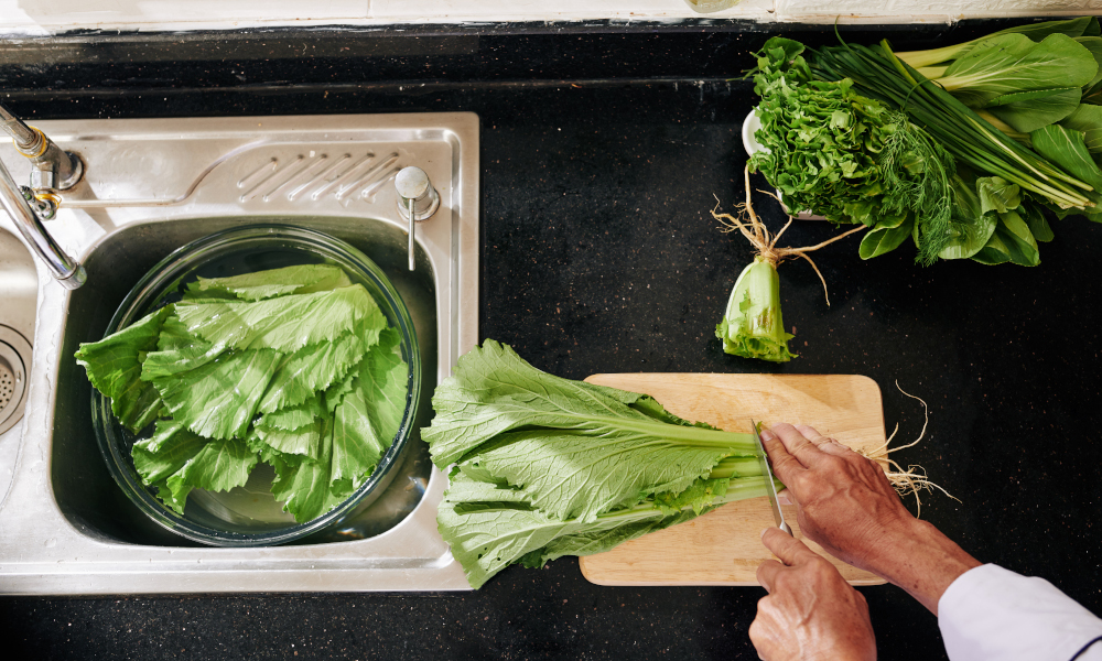 Man cutting lettuce and putting leaves in big bowl with fresh water in kitchen sink