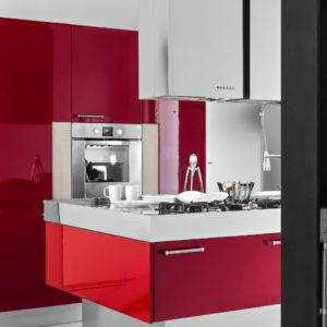 Interiors of a modern kitchen with red themed island and cabinets