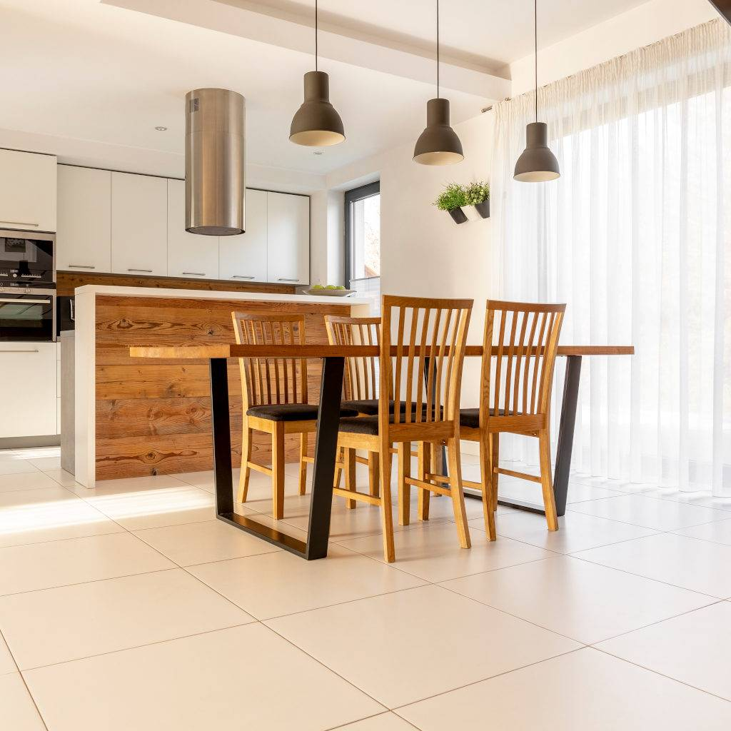 Spacious, open kitchen and dining room with wooden table and chairs, large window, white cupboards and tiles on the floor