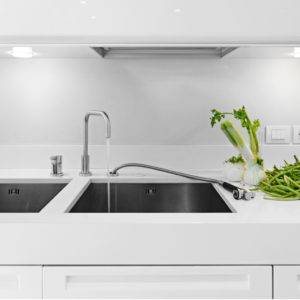 White kitchen theme with stone countertop, handle-free cabinets and stainless steel undermount sink