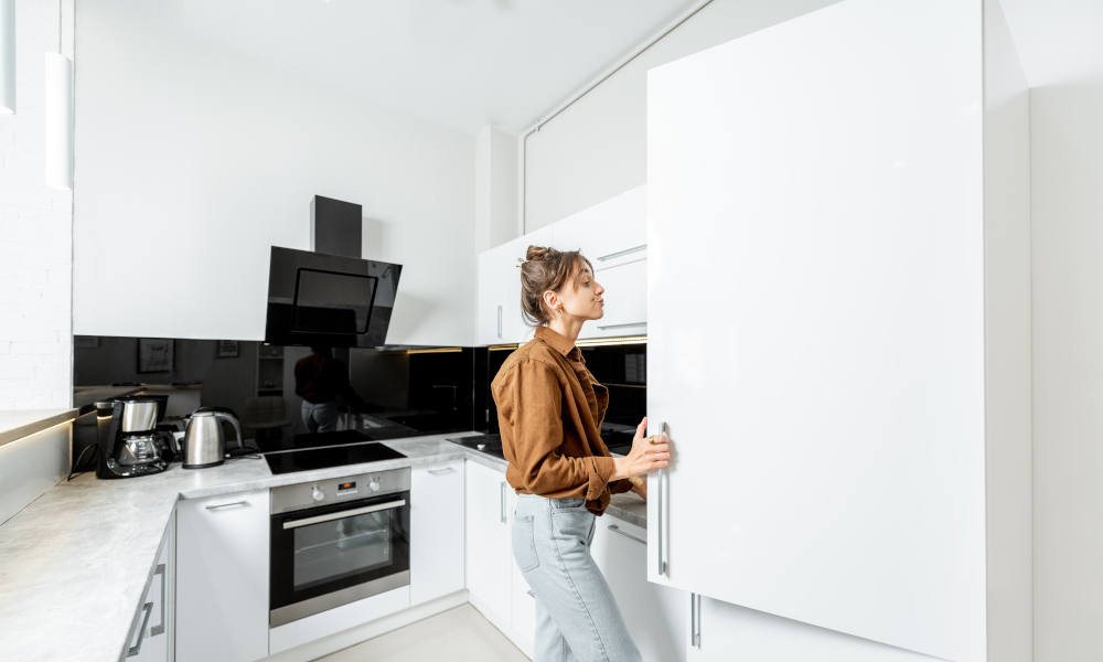 Woman opening a spacious kitchen cabinet in white