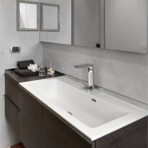 Interior view of a modern bathroom in foreground the built-in washbasin into the wooden furniture above on it there is a mirror with wall lamp