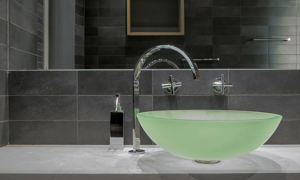 A light green glass countertop washbasin and steel tap in the modern bathroom