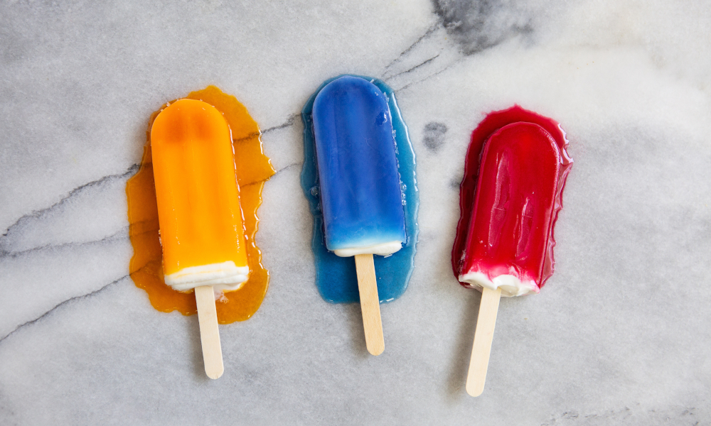 Orange, blue and red popsicles melting on a marble countertop in the heat