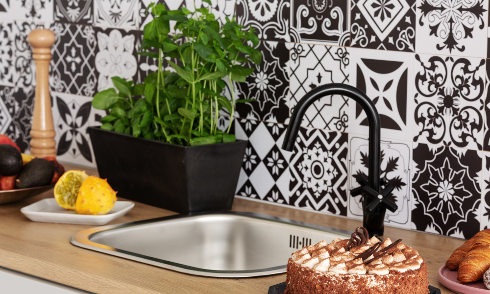 Cake, Herbs and fruits on kitchen counter in bright kitchen interior with trendy tiles on the wall